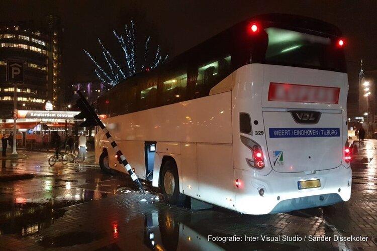 Touringcar rijdt verkeerslicht uit de grond bij Centraal Station in Amsterdam