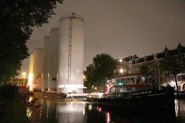 Metershoge silo's door Amsterdamse grachten vervoerd