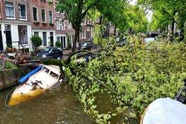 Boom valt op boot in gracht Amsterdam