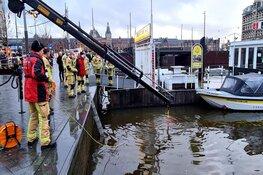Canta brommobiel belandt in het water bij de Damrak in Amsterdam